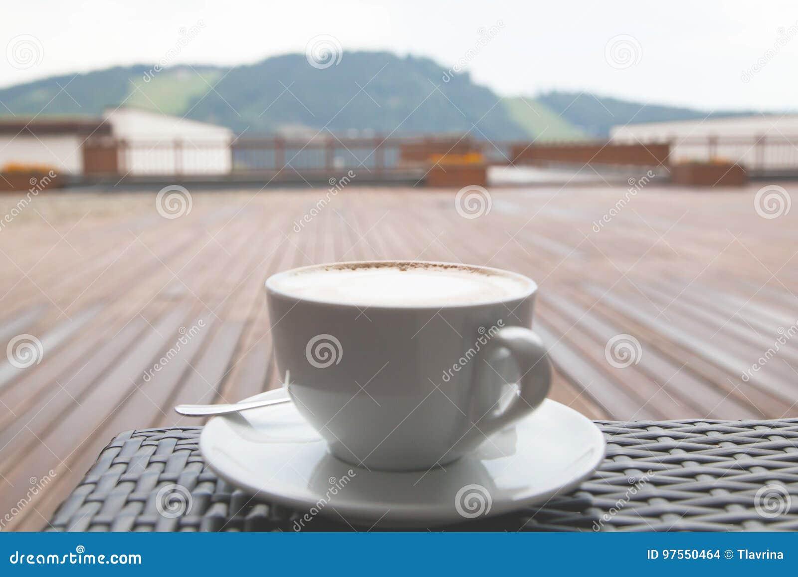 Мягкий конец фокуса вверх по чашке кофе latte capuccino на деревянном backgr