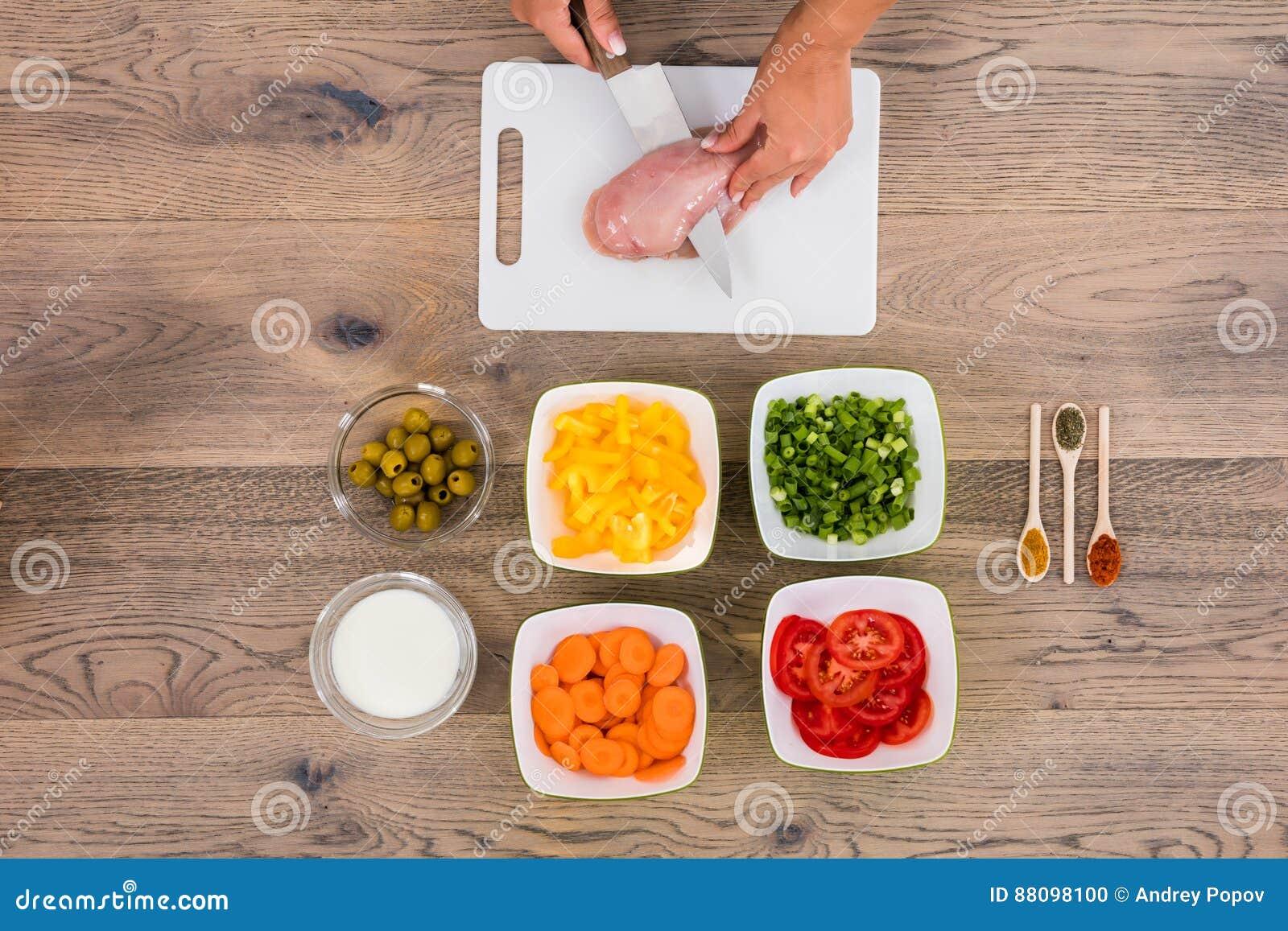 Мясо вырезывания персоны на прерывая доске