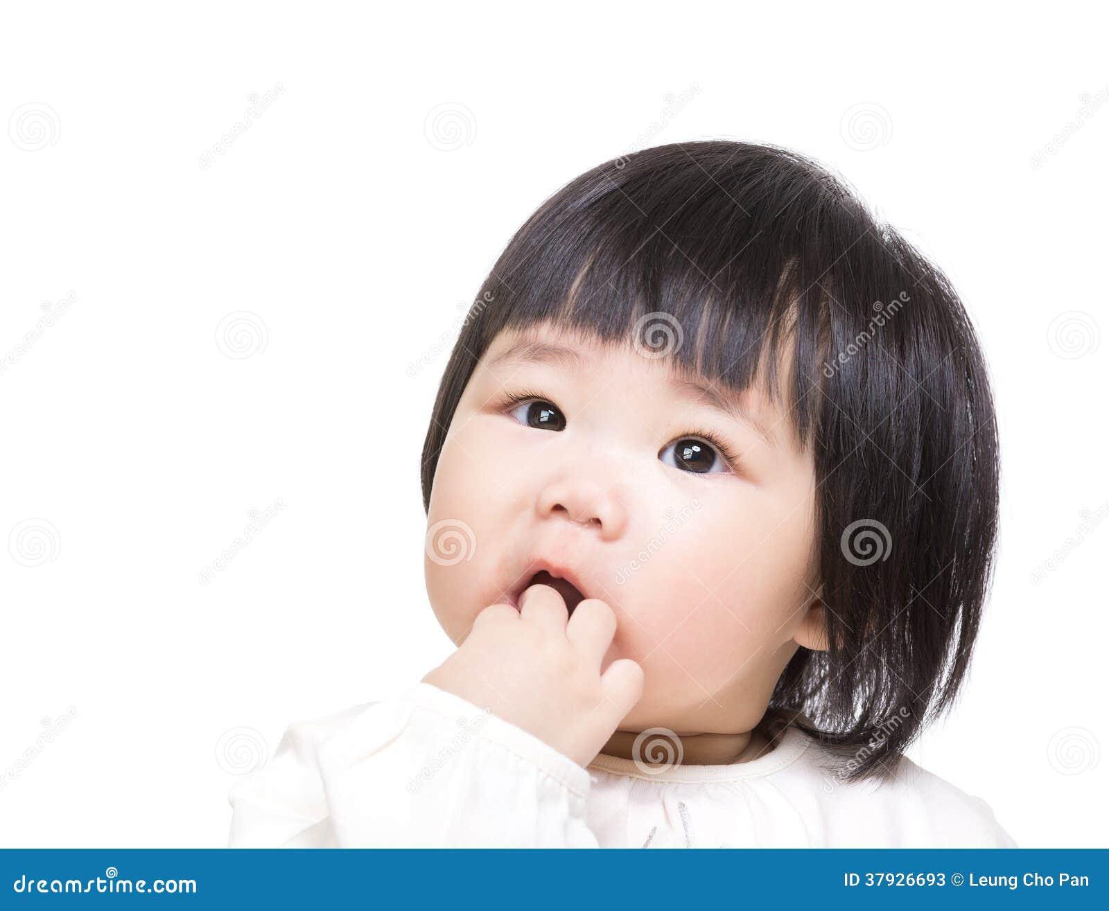 Младенец Азии всасывает палец в рте