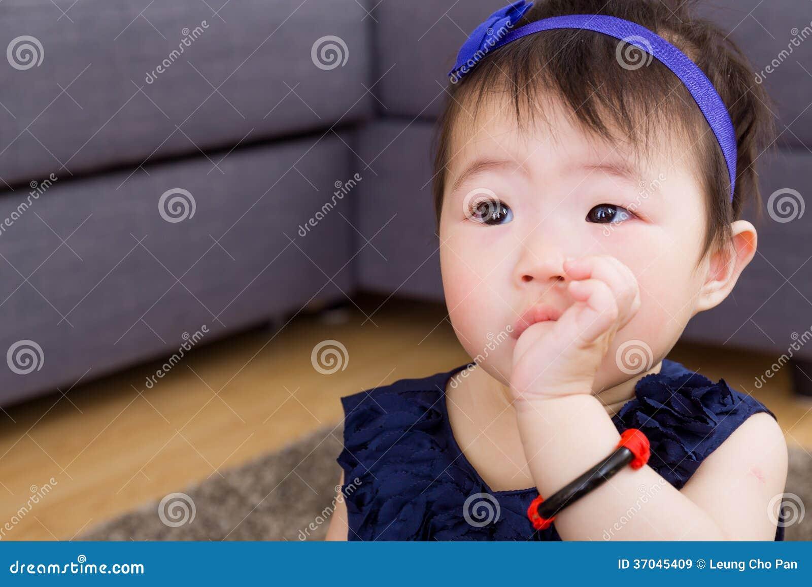 Младенец всасывая палец в рте