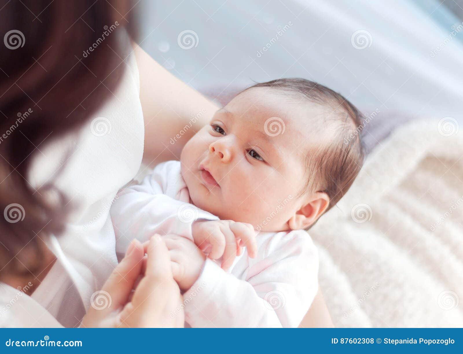 младенец ее мать newborn Мать держит ее маленького младенца