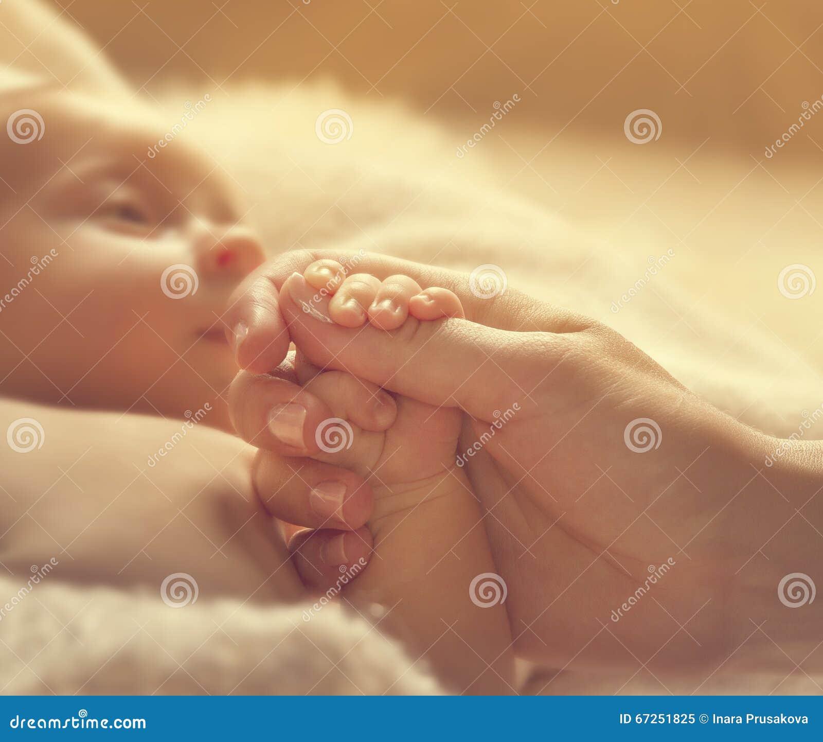 Младенец держа руки матери, больное Newborn здоровье, помощь новорожденного