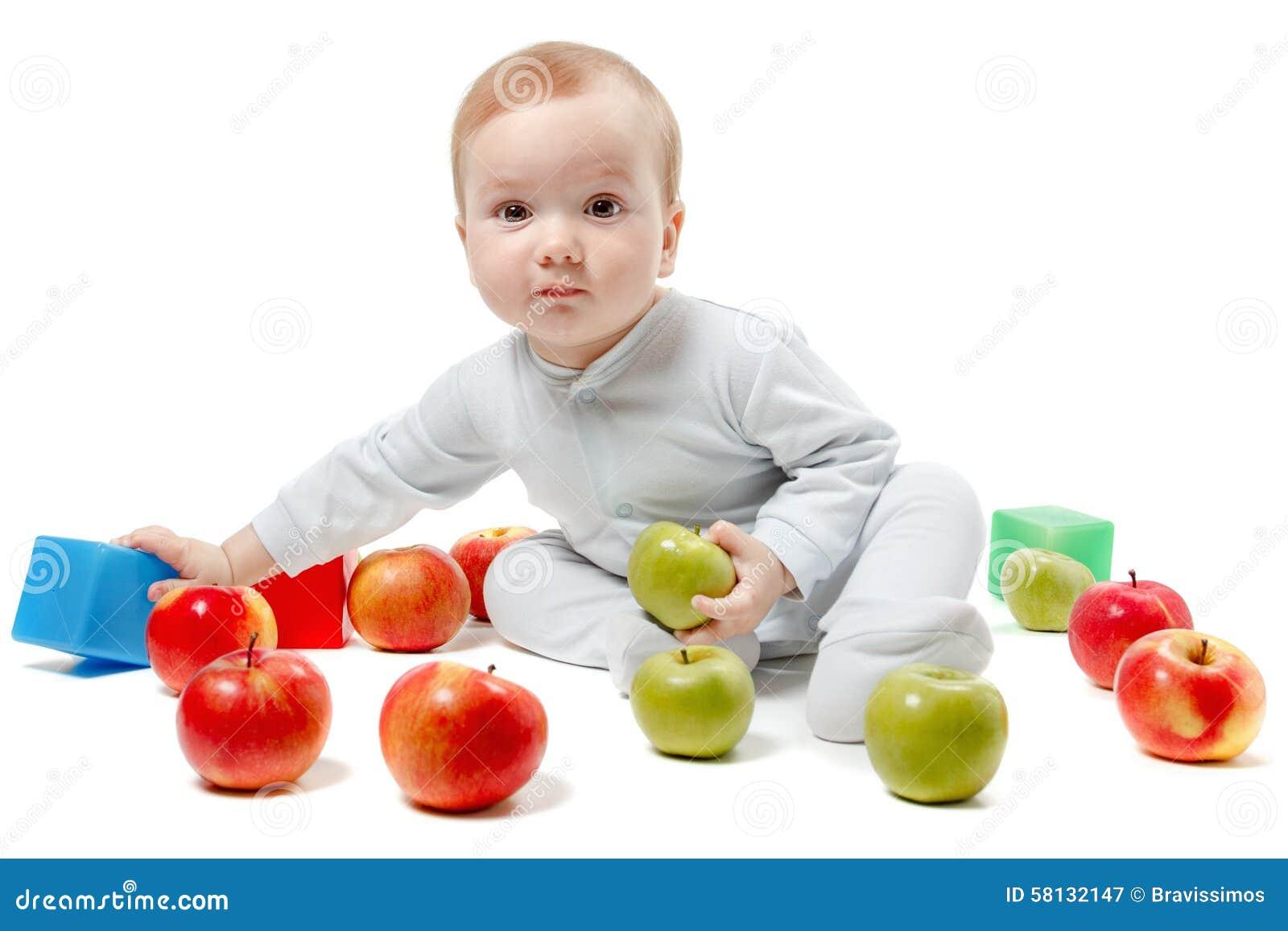Младенец играет с яблоками и игрушками Портрет студии, изолированный на белой предпосылке