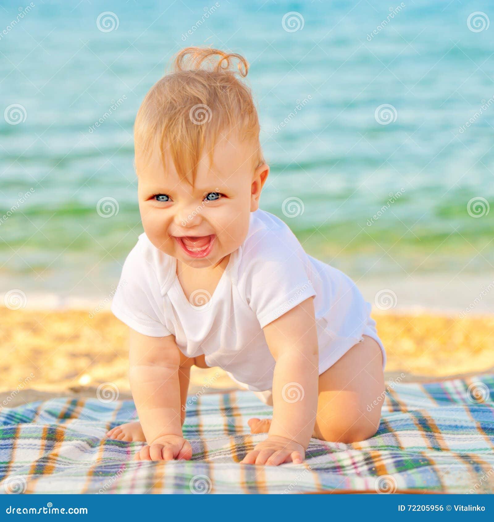 Младенец играя на пляже около моря