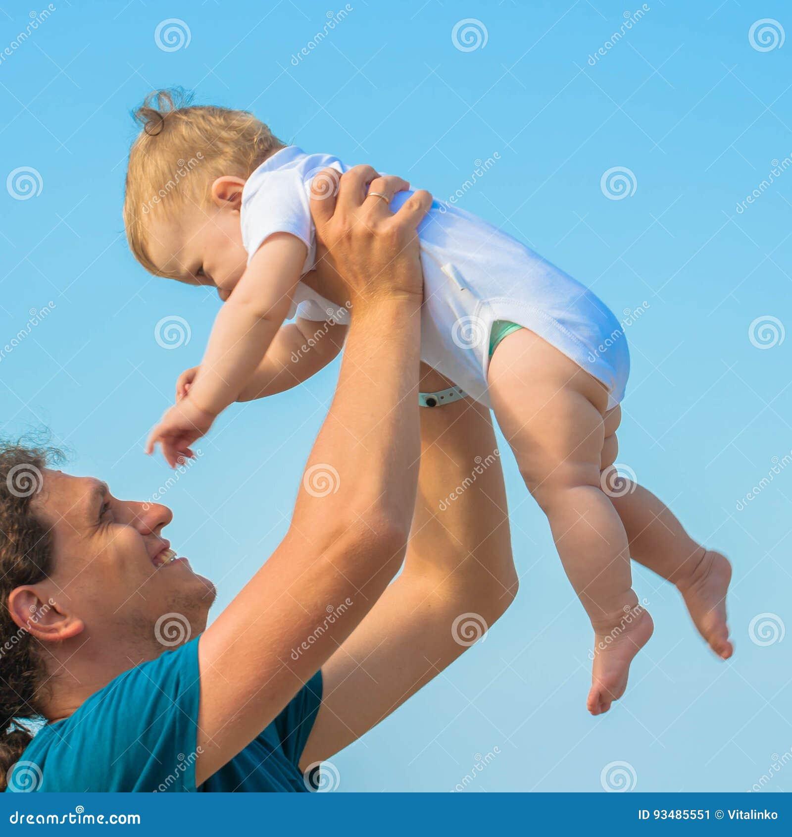 Младенец и отец имея потеху совместно на пляже