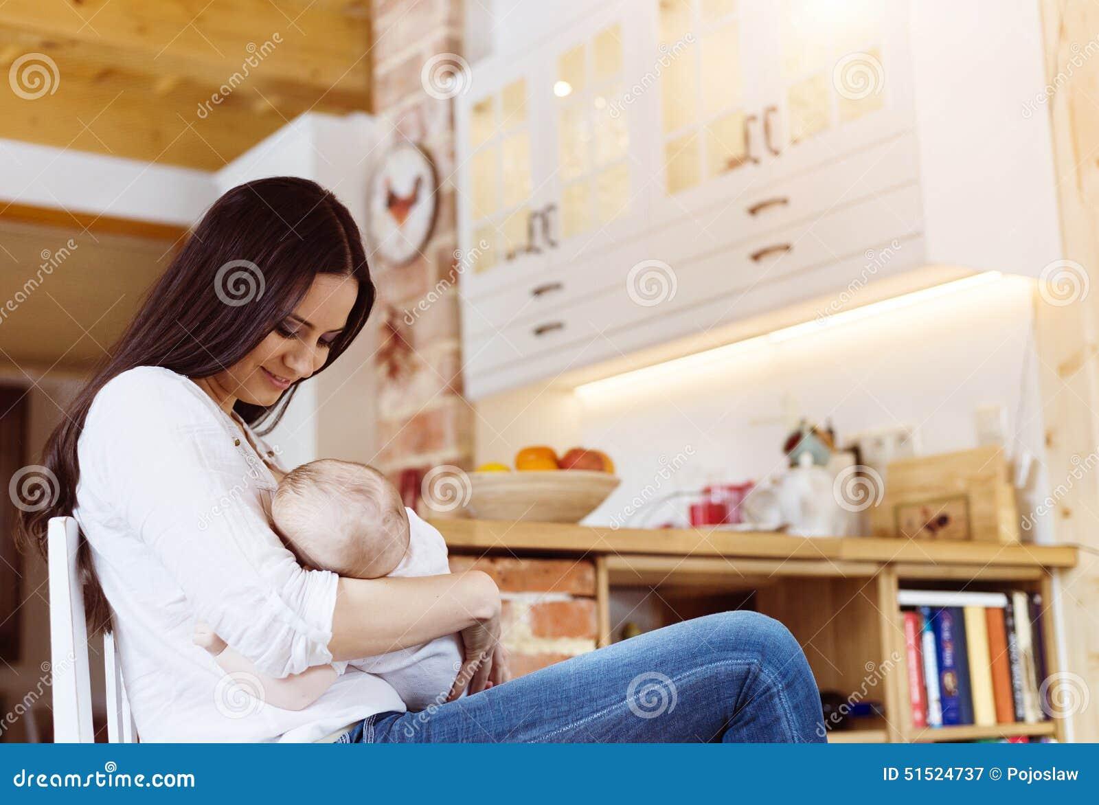 младенец кормя ее мать грудью