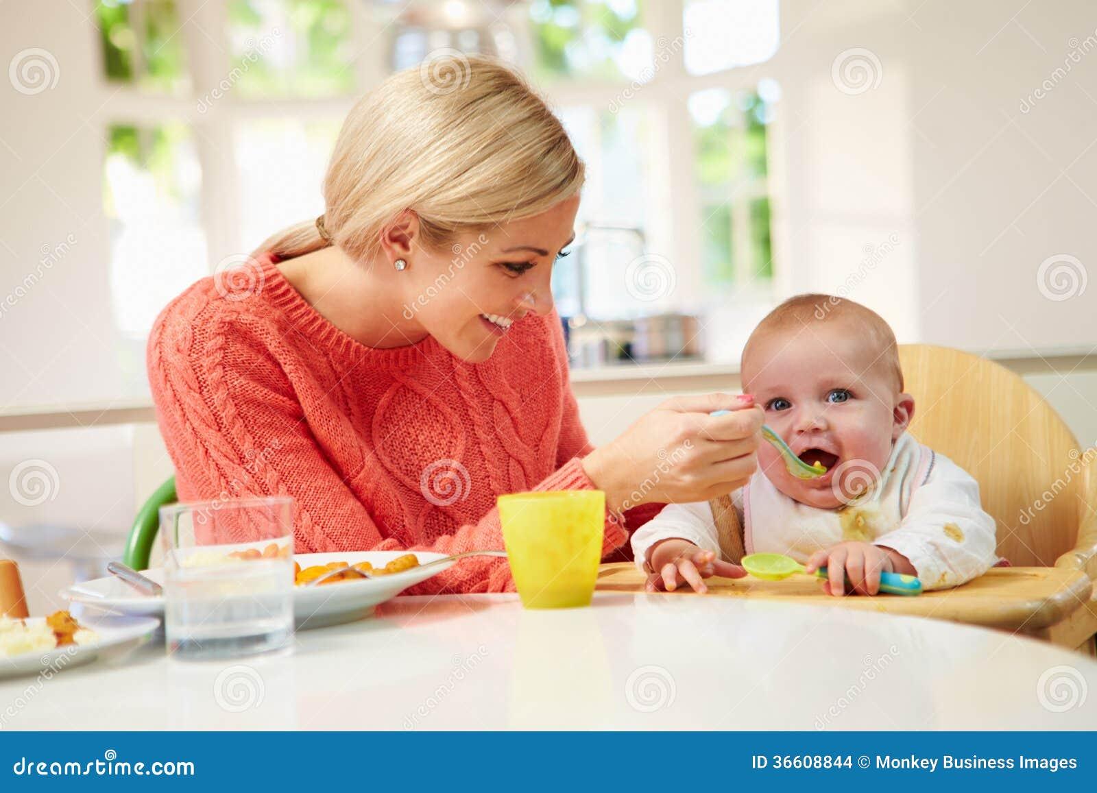 Младенец матери подавая сидя в высоком стуле на времени принятия пищи