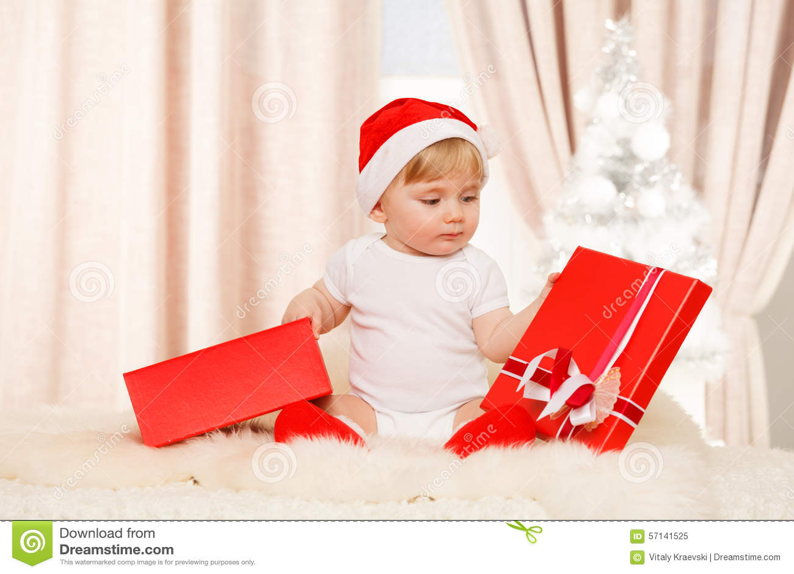 Младенец santa держит большую красную подарочную коробку