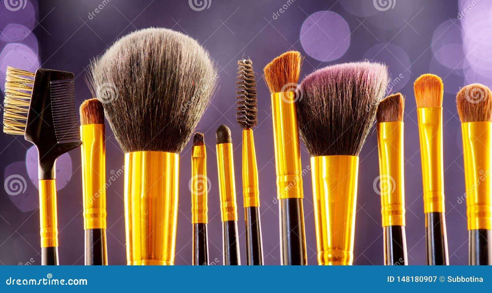 Набор щеток макияжа над черной праздника моргать предпосылкой Различный профессионал составляет щетку на темном фоне в студии