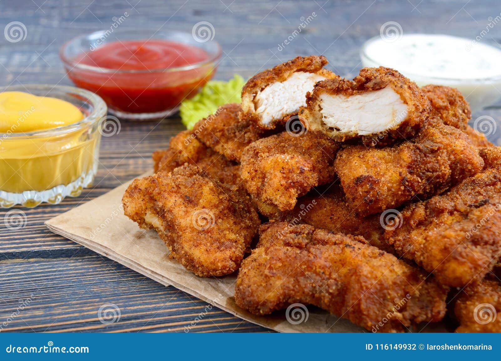 Наггеты цыпленка Части глубок-зажаренного кудрявого мяса, на бумаге с различными соусами на деревянном столе