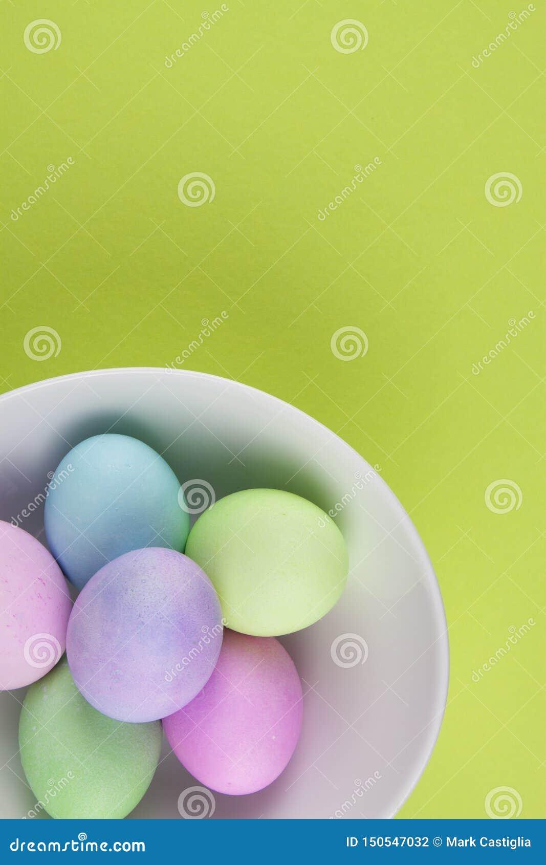 Надземный взгляд ярко покрашенных пасхальных яя в белом шаре на зеленой предпосылке