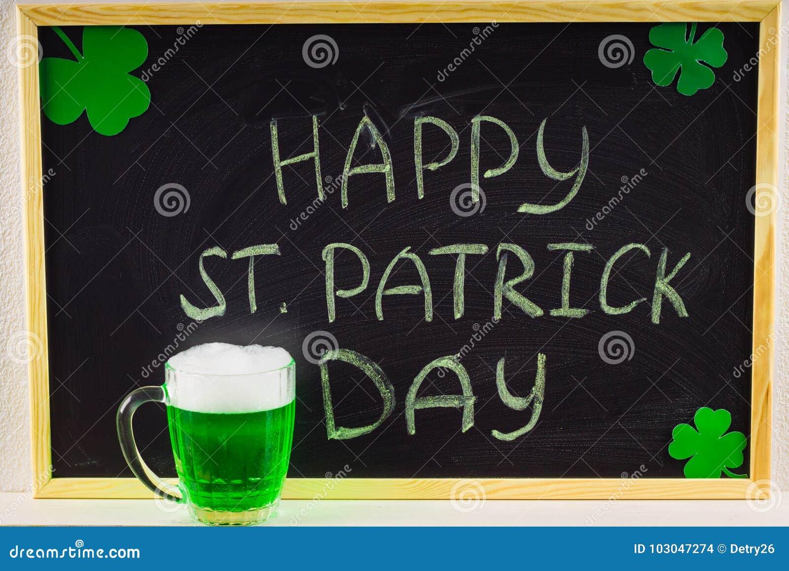 Надпись с зеленым мелом на доске: День счастливого St. Patrick листья клевера Кружка с зеленым пивом