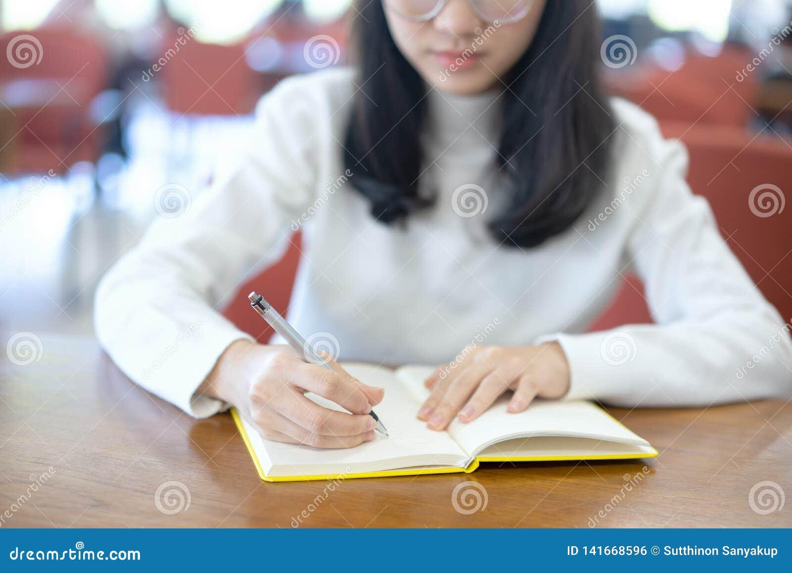 Назад к концепции университета коллежа знания школьного образования, молодая бизнес-леди сидя на таблице и принимая примечания в
