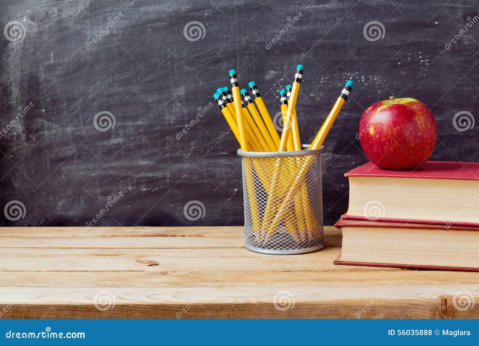 Назад к предпосылке школы с книгами, карандашами и яблоком над доской