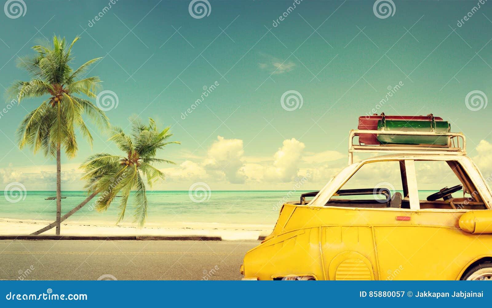 Назначение перемещения: винтажный классический автомобиль припарковал около пляжа с сумками на крыше