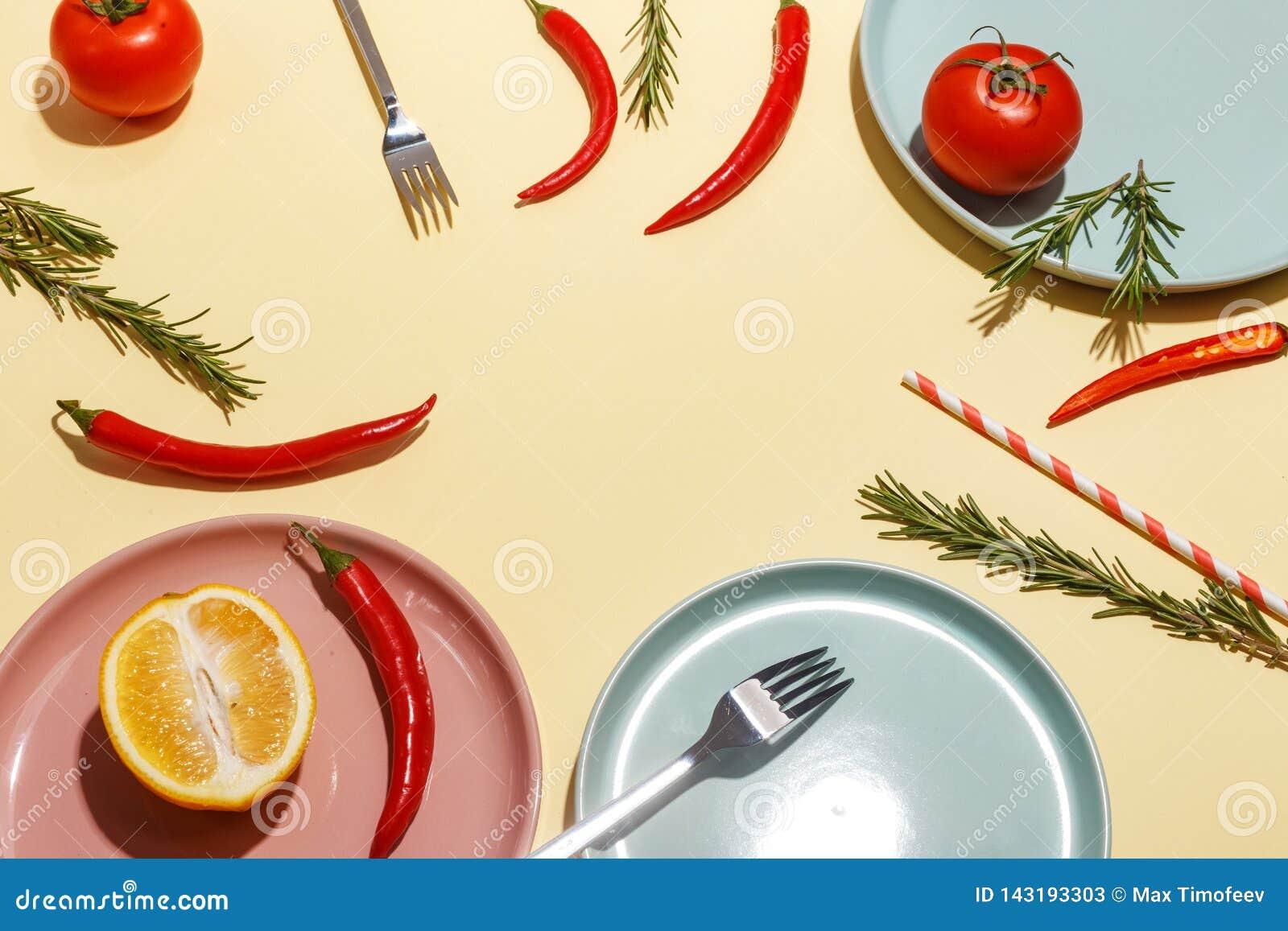 Накаленные докрасна перцы, томаты, розмариновое масло и специи на ligth-желтой предпосылке Сервировка стола r