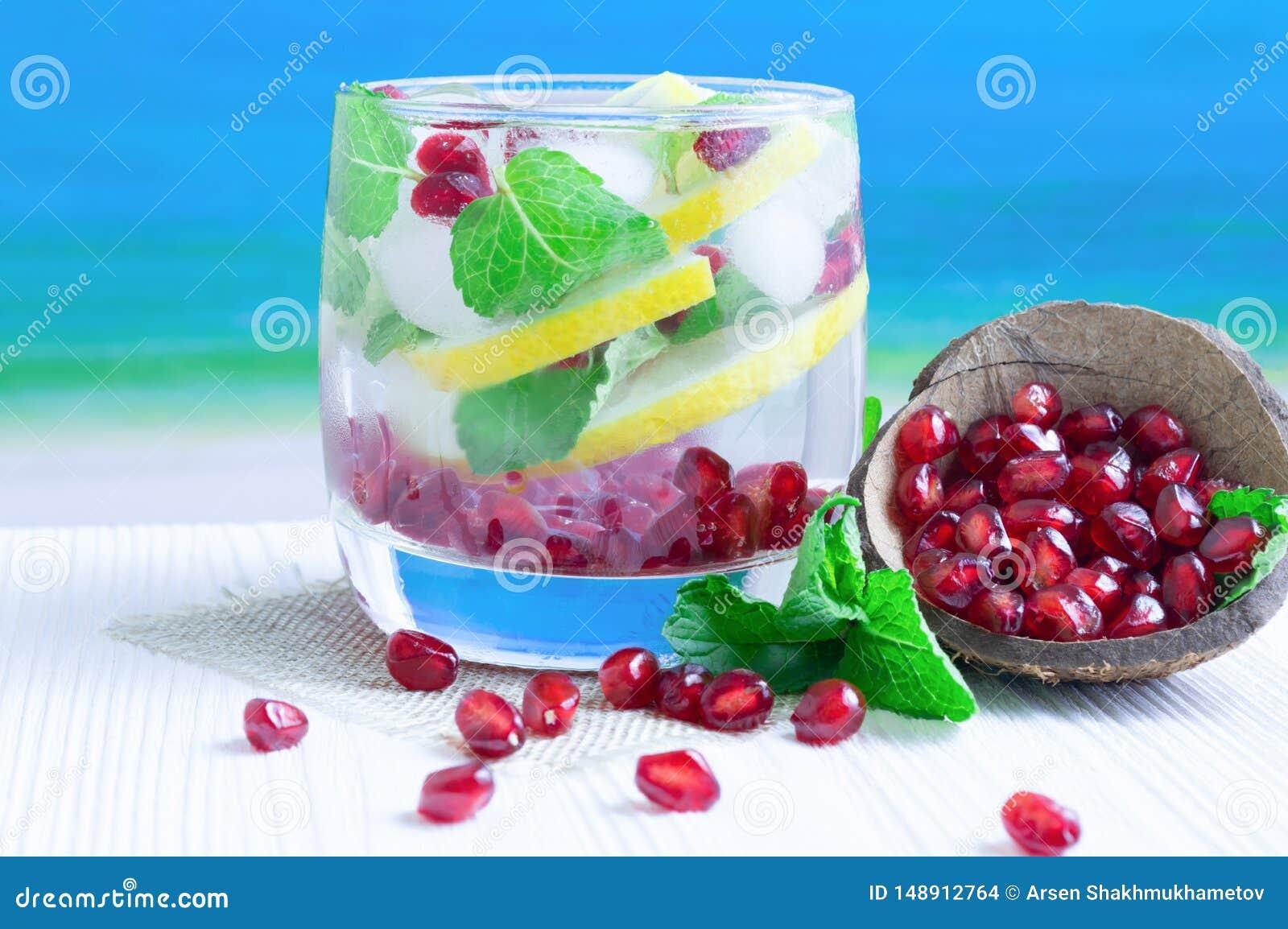Напиток лета лимона, гранатового дерева и мяты на белом деревянном столе против моря