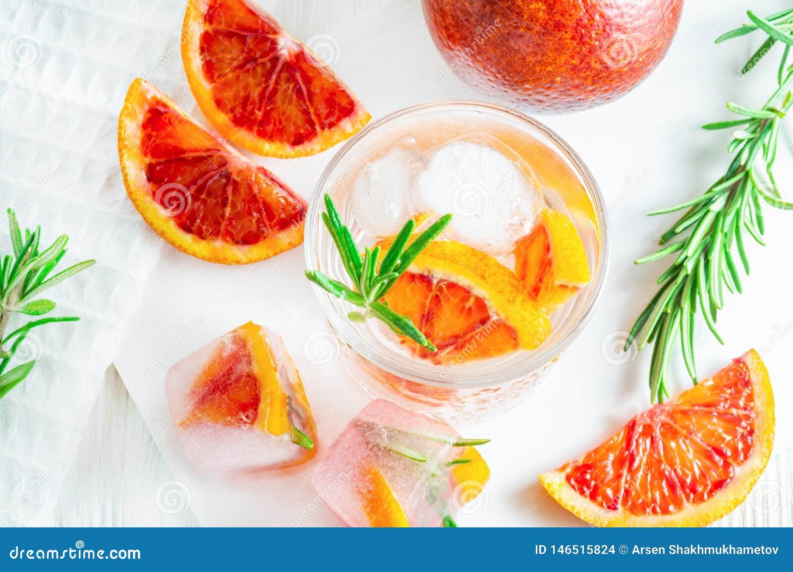 Напиток лета с апельсином и розмариновым маслом крови на белой деревянной предпосылке Плоск-положение, взгляд сверху
