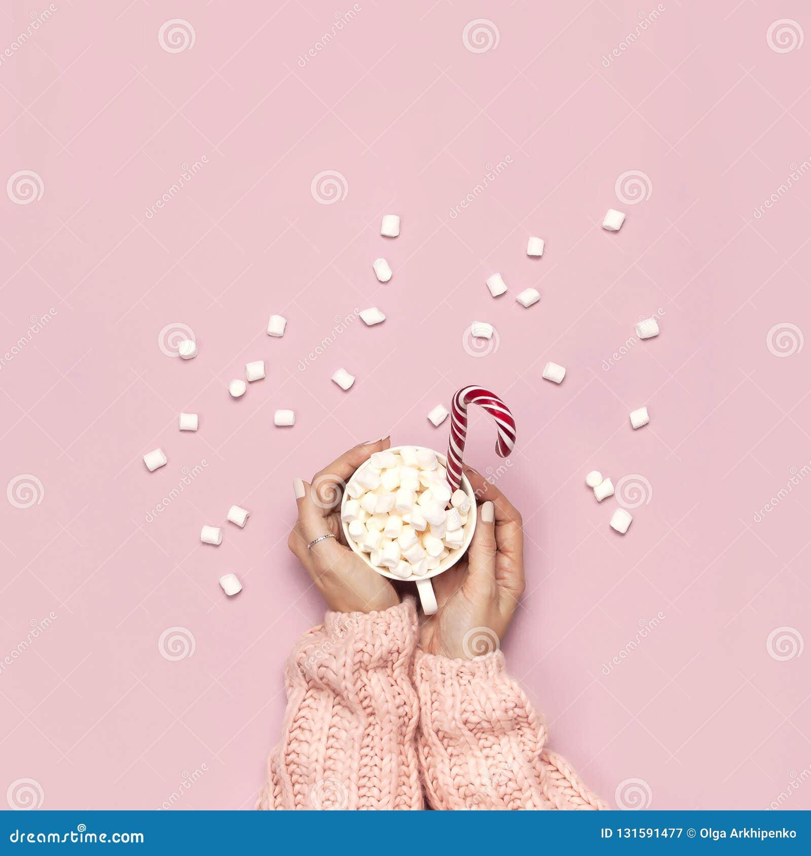 Напиток Нового Года рождества, белая кружка с зефирами в женских руках в связанной тросточке свитера и конфеты на розовой верхней