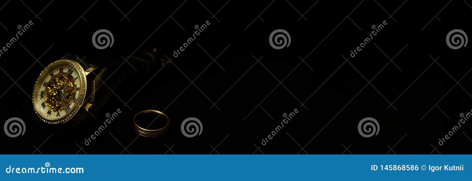 Наручные часы и кольцо людей на черном бархате