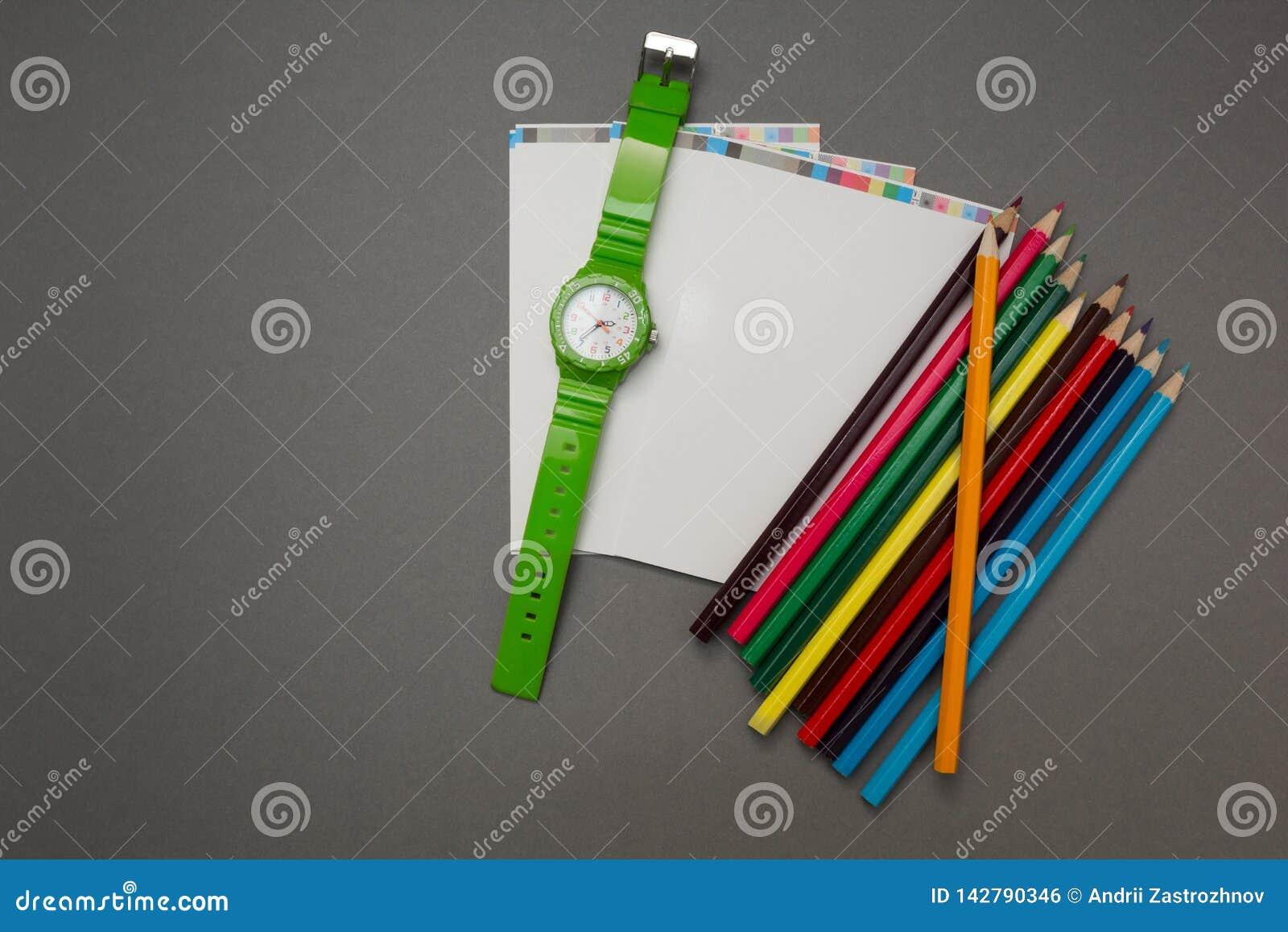 Наручные часы, тетрадь и карандаш на серой предпосылке