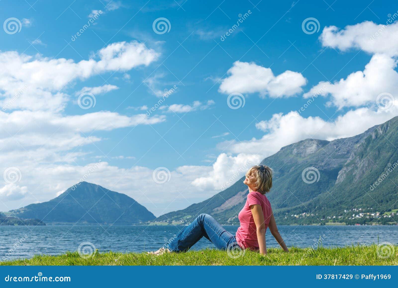 Наслаждаться женщины ослабляя на побережье фьорда
