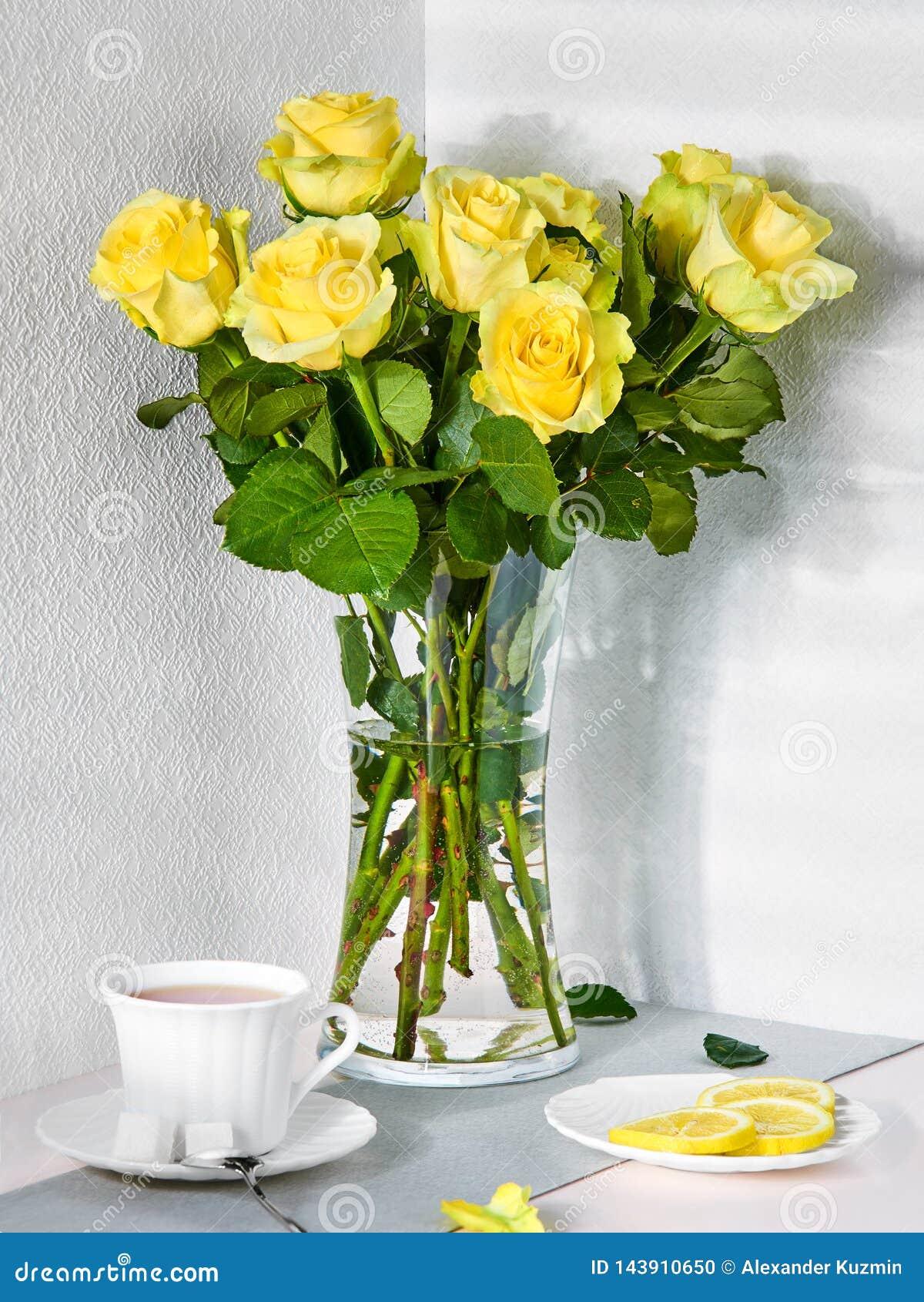 Натюрморт с букетом желтых роз и чашки чаю