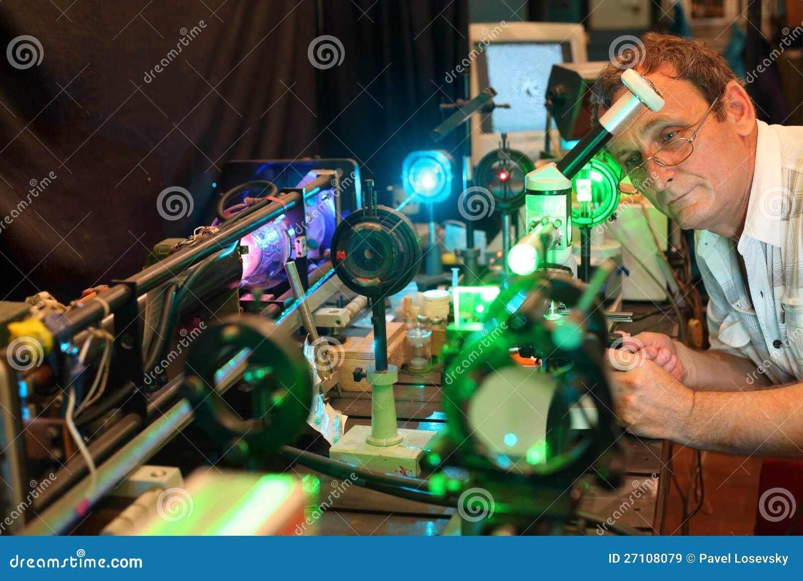Научный работник с стеклом демонстрирует лазер