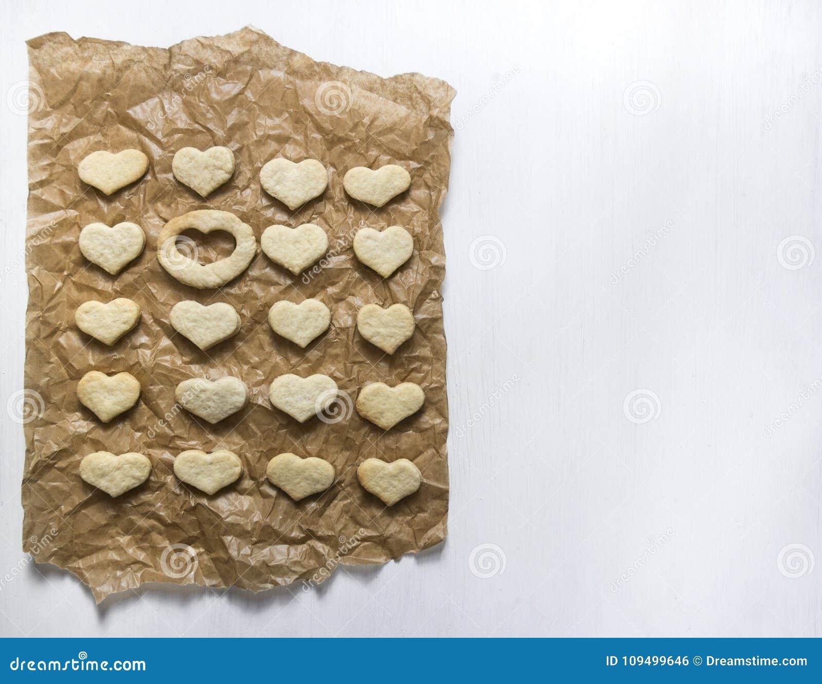 На белой предпосылке на лож бумаги выпечки печенье в форме сердца и одного места пусто