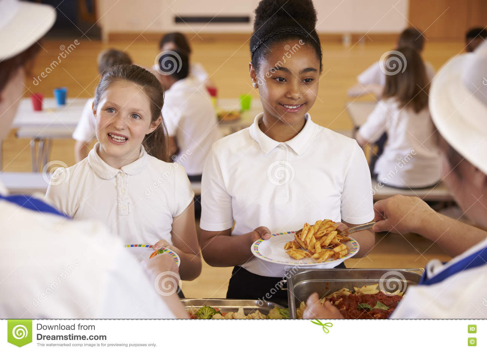 Над взглядом плеча девушек будучи послуженным в школьном кафетерии