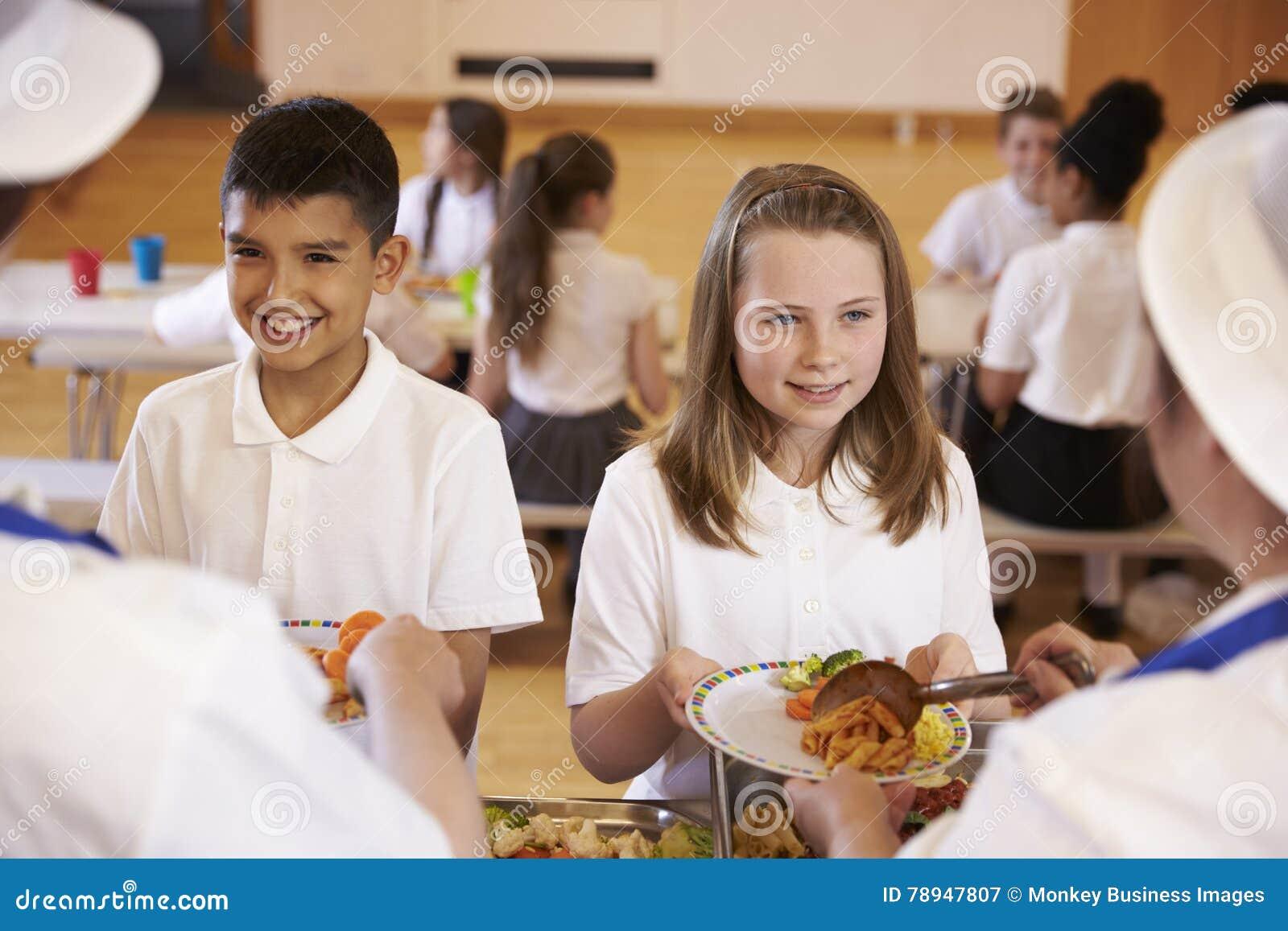 Над взглядом плеча детей будучи послуженным в школьном кафетерии