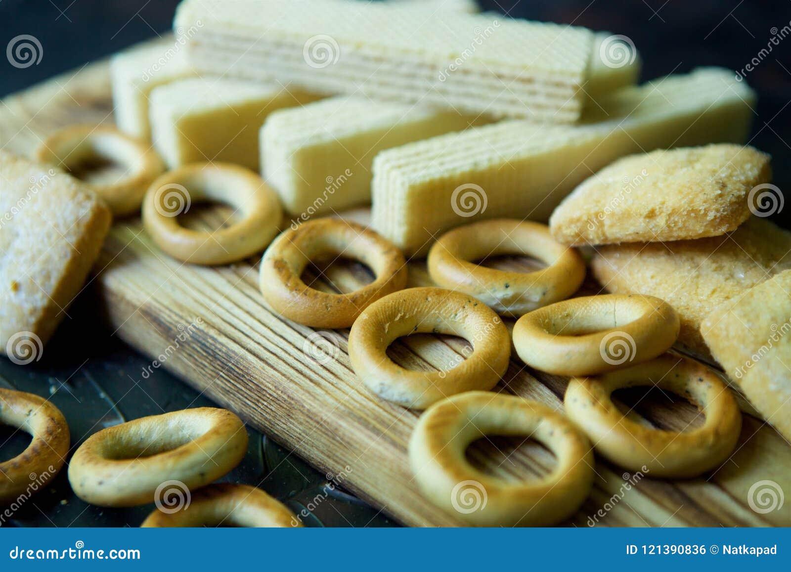 На деревянной доске бейгл, waffles и печенья