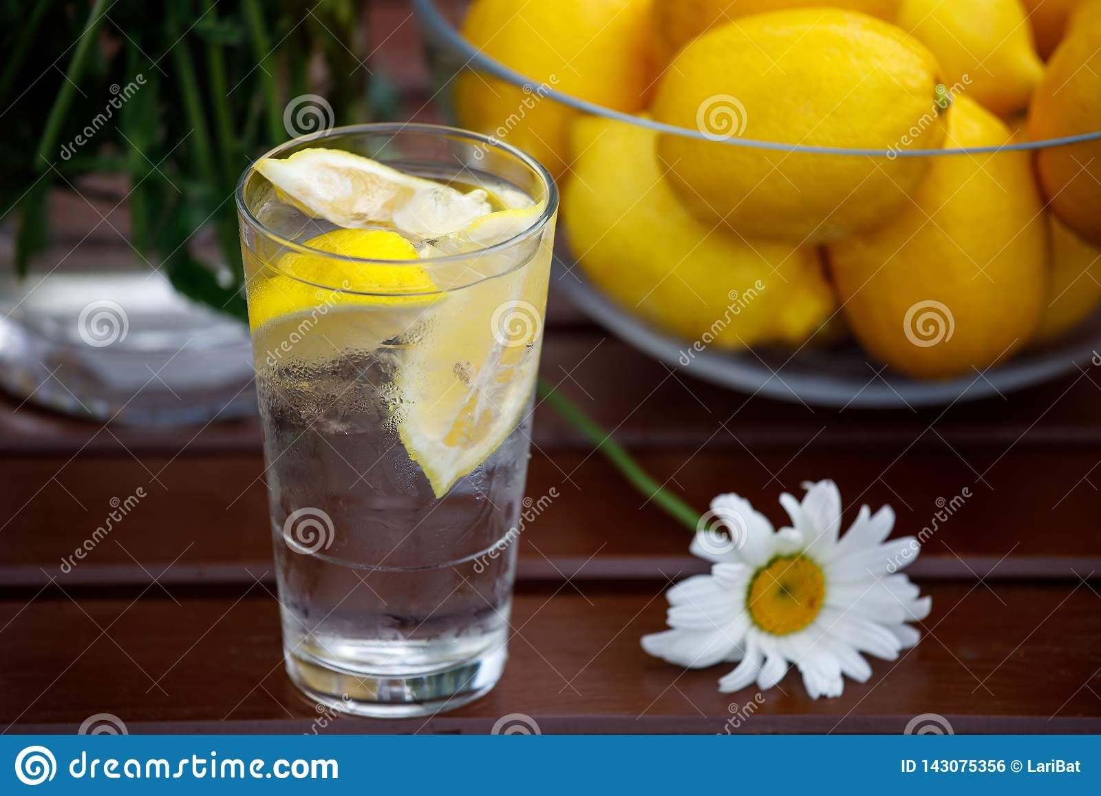 На деревянном столе стекло воды с лимоном и ваза лимонов