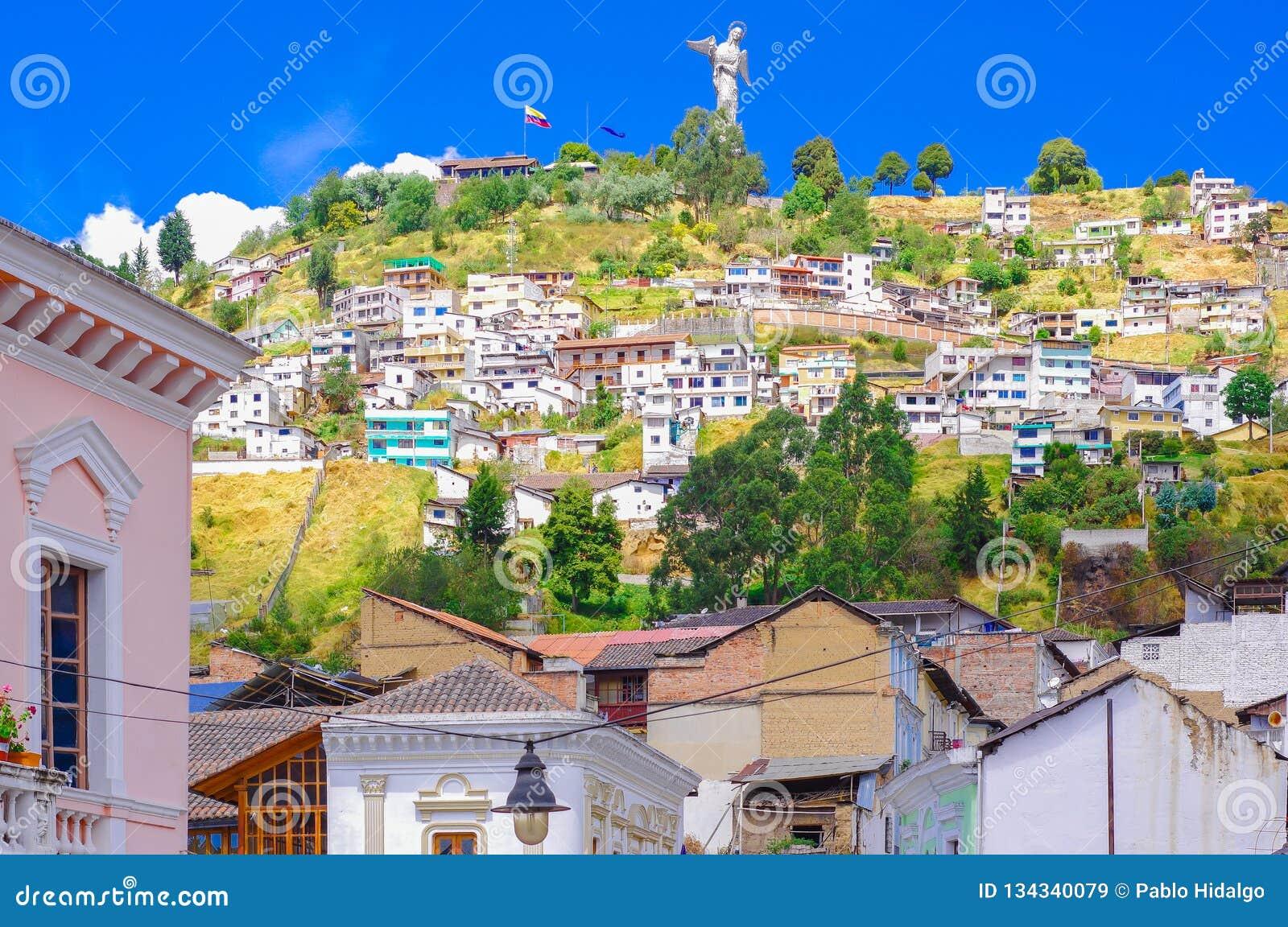 На открытом воздухе взгляд колониальных домов зданий расположенных в городе Кито со статуей девственницы Panecillo в