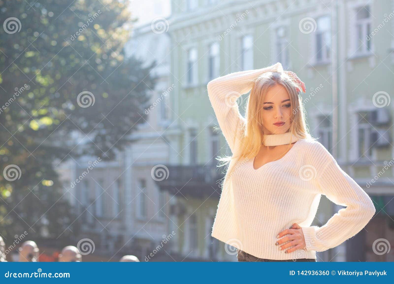 На открытом воздухе портрет роскошной модели нося стильное обмундирование представляя на улице с естественным светом солнца Пусто
