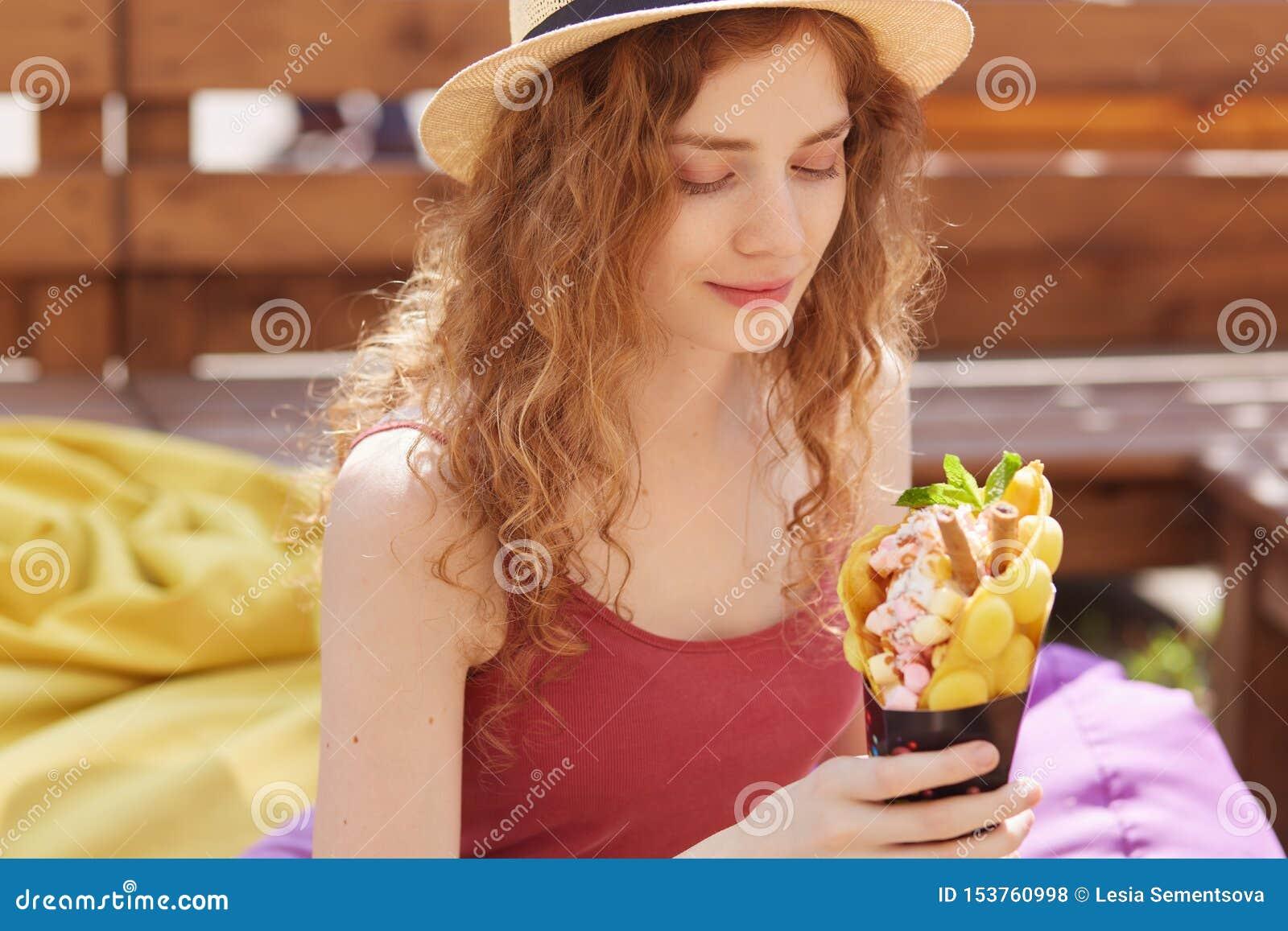 На открытом воздухе съемка романтичной милой маленькой девочки смотря ее десерт, находящся в высоких духах, чувствуя голоде, держ