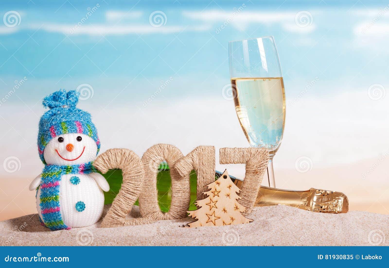 Надпись 2017, шампанское, снеговик рождества в песке
