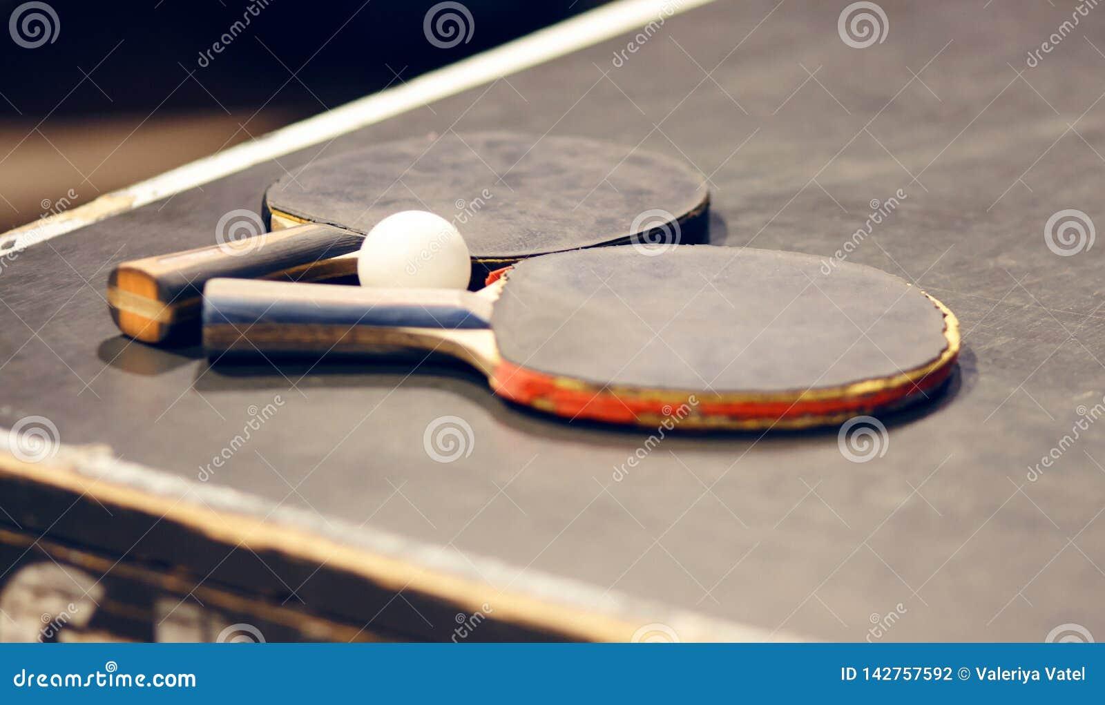 На таблице 2 старых ракетки настольного тенниса и шарик