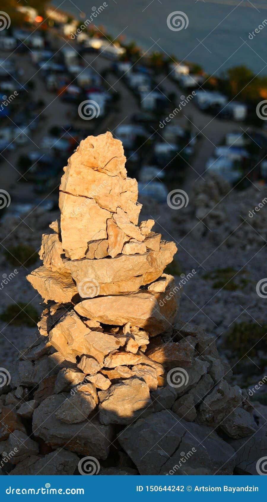 Небольшая куча камней в горах во время захода солнца, близкий взгляд