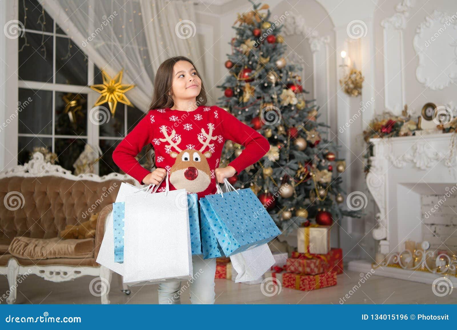небольшая счастливая девушка на рождестве Рождество Ребенк наслаждается праздником счастливое Новый Год кладет покупку в мешки sa