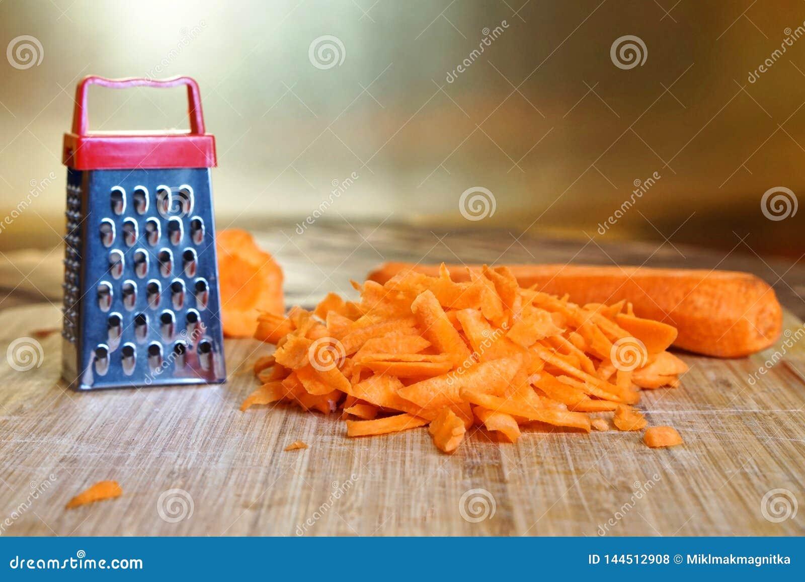 Небольшая терка и большая морковь на разделочной доске Необыкновенные тайна и обман зрения