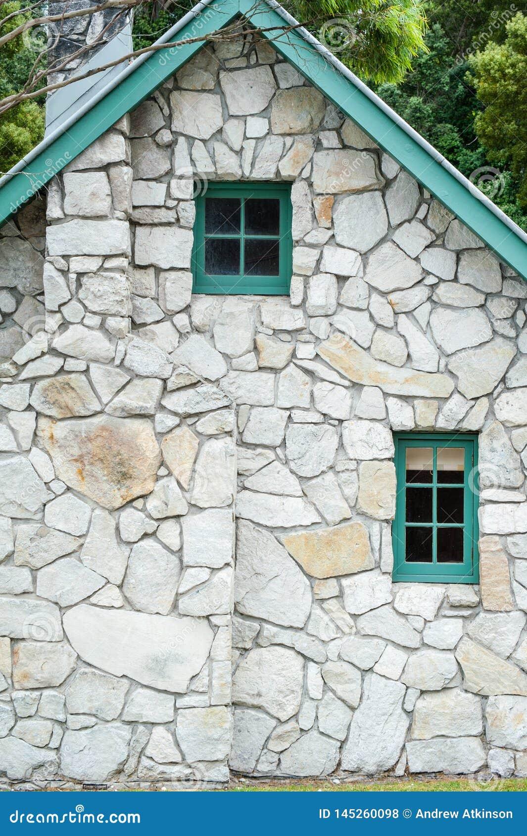 Небольшие деревянные окна и стог камина в каменном коттедже с зеленым