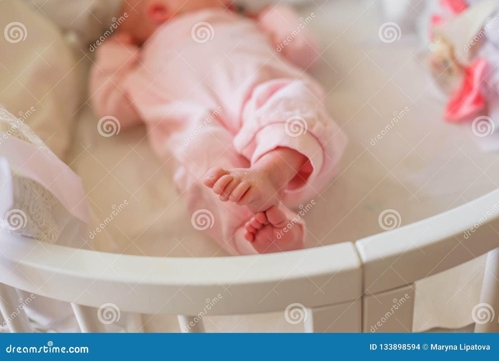 Небольшие ноги младенца одетые в розовом romper Крошечные пальцы newborn Ребенок пересекал ноги и лож в круглой белой кровати