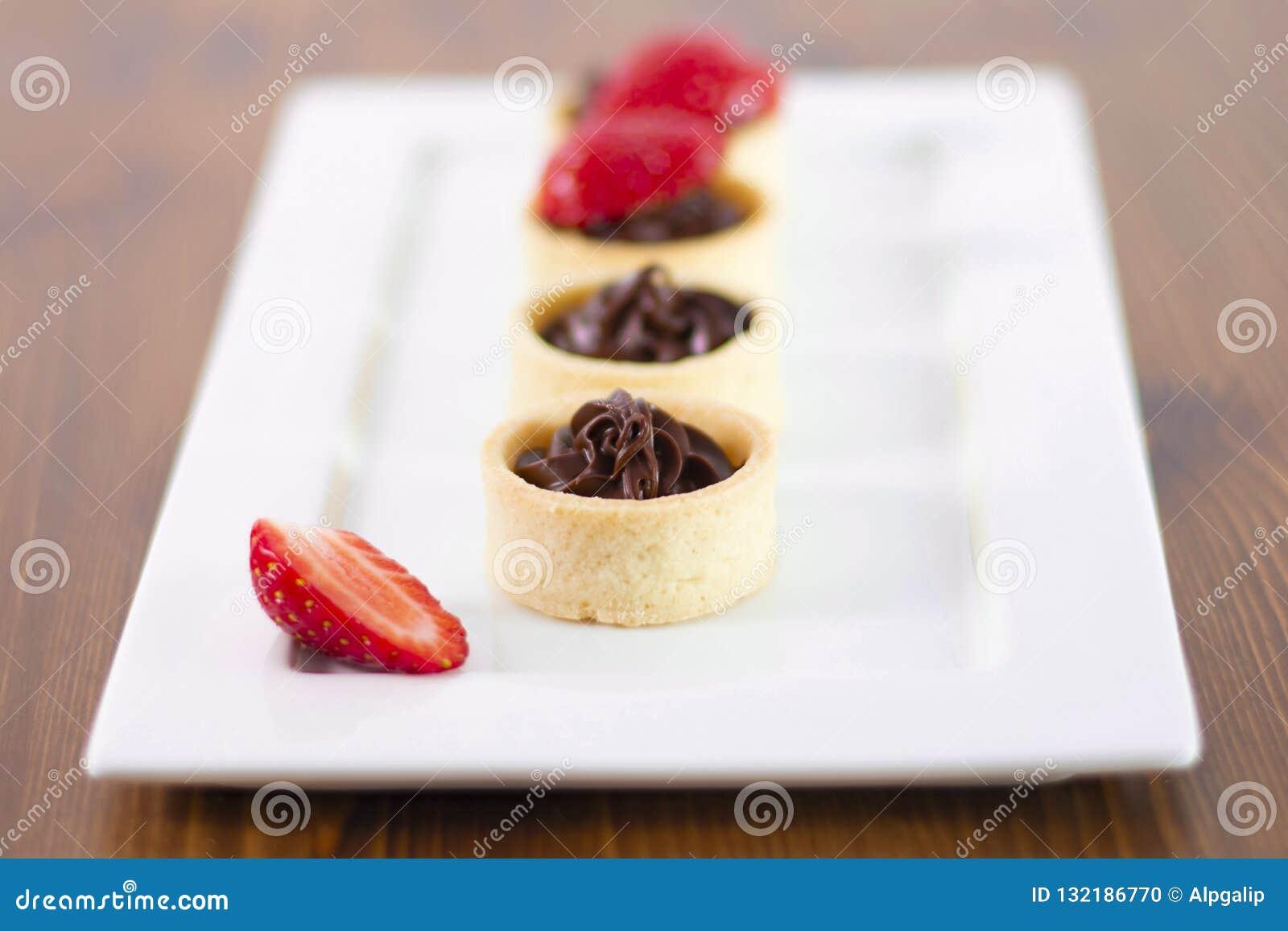 Небольшие пироги шоколада со свежей клубникой