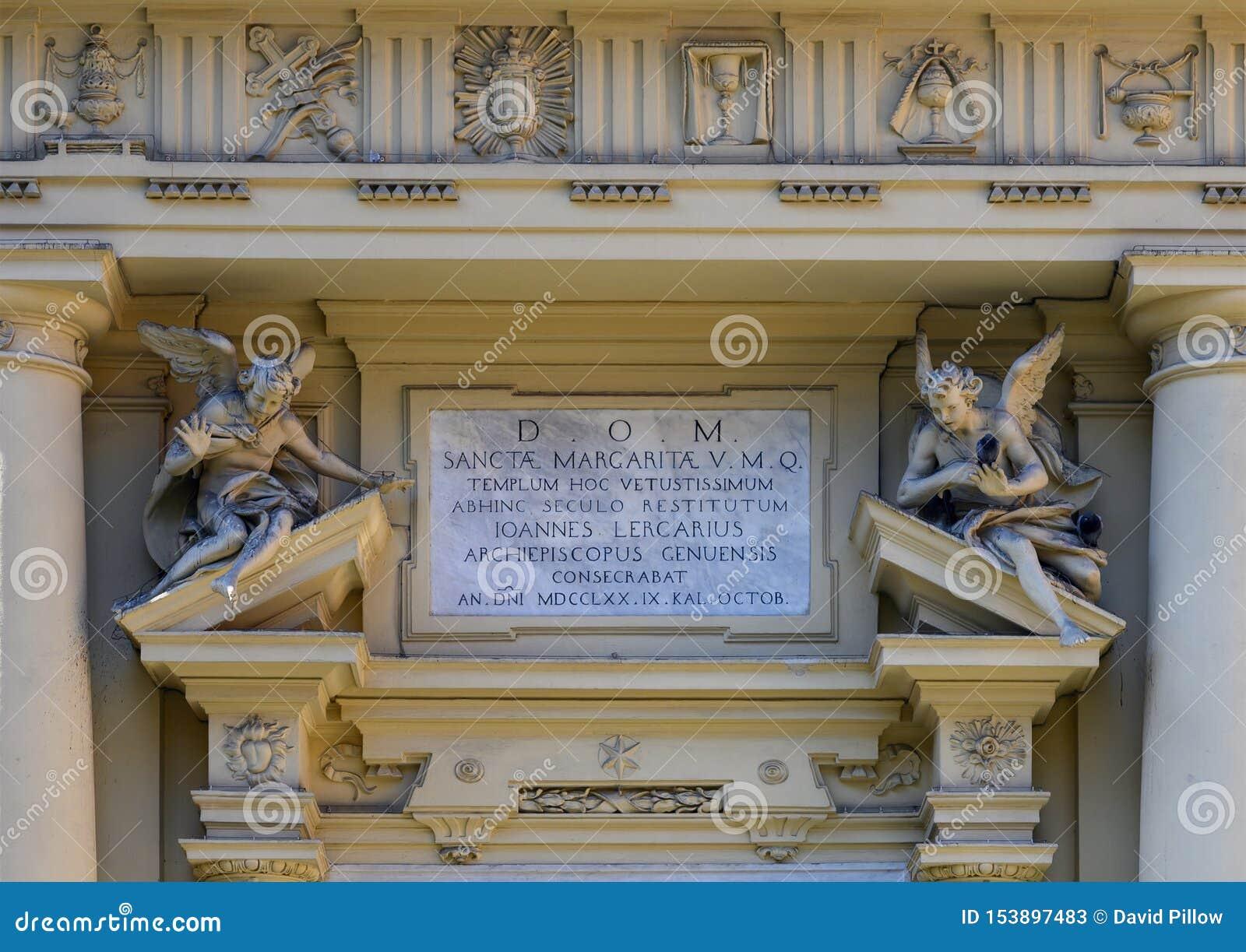 Небольшие статуи и металлическая пластинка информации над главным входом к базилике St Margaret Antiochia, Санта Margherita Ligur