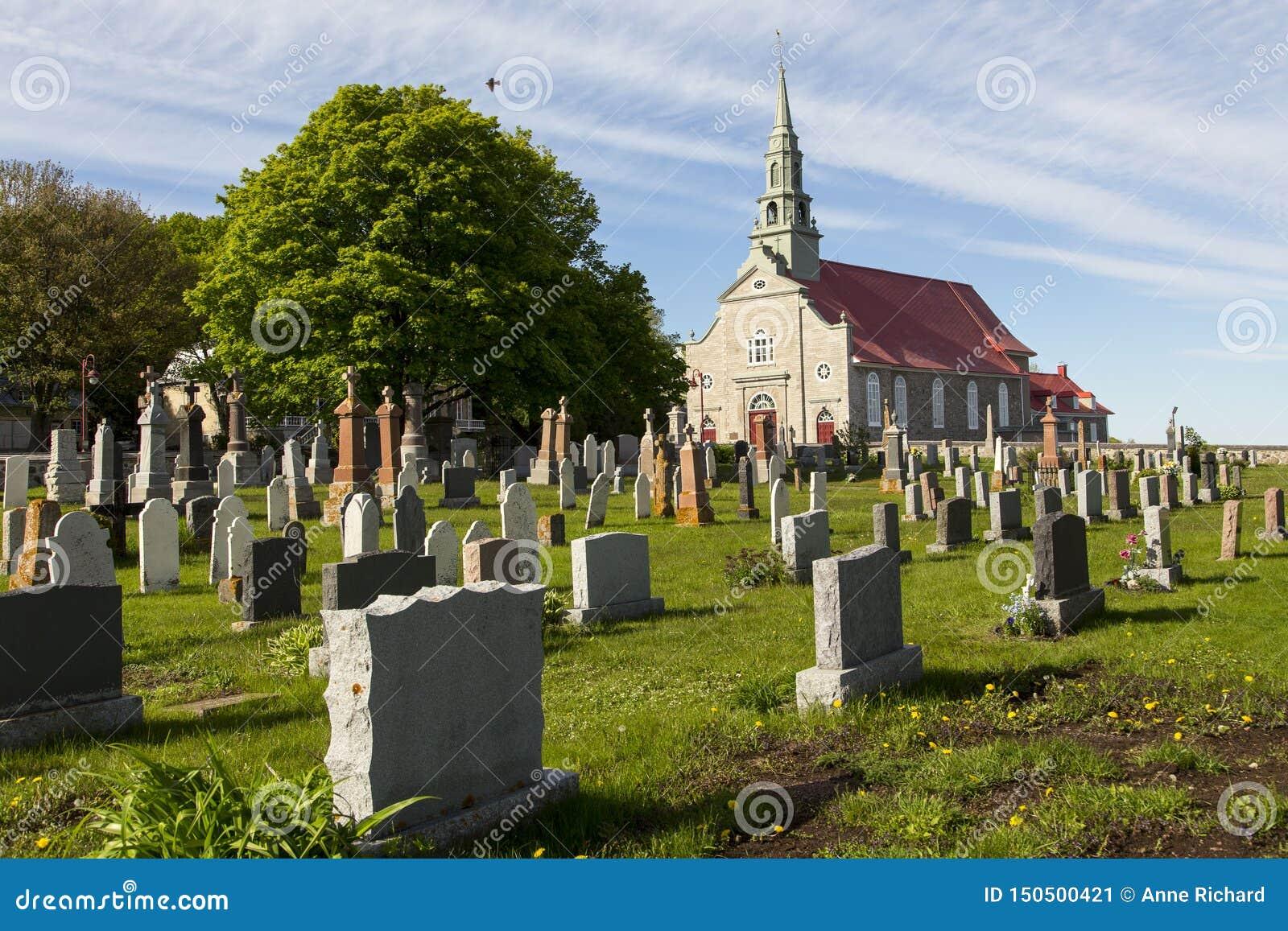 Небольшое кладбище деревни и каменная католическая церковь patrimonial неоклассические 1737 в Свят-Джин, острове Орлеана