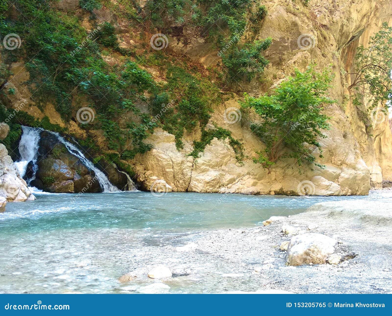 Небольшой водопад в горах. Жаркий летний солнечный день.