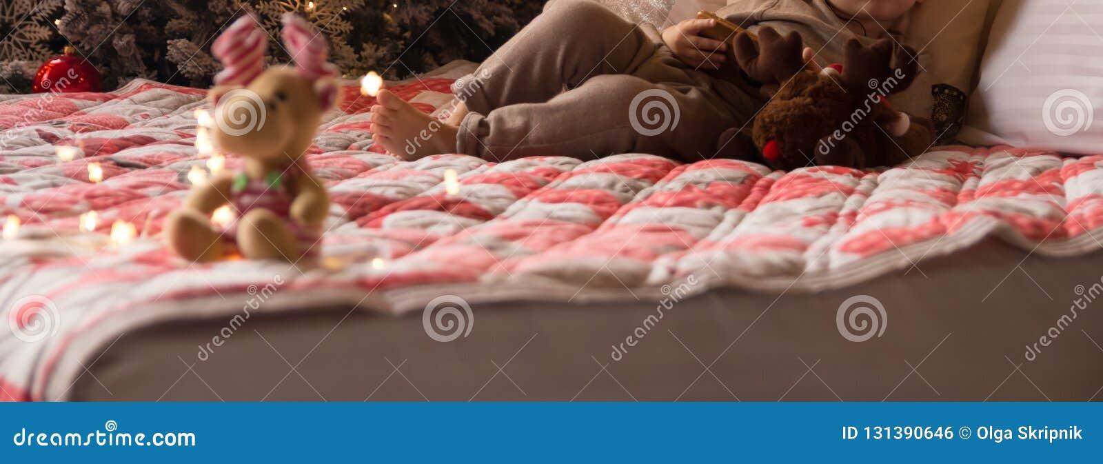 Небольшой ребенок лежит на кровати с лосем около дерева Нового Года, держит телефон, планшет пуща рождества knurled зима снежных