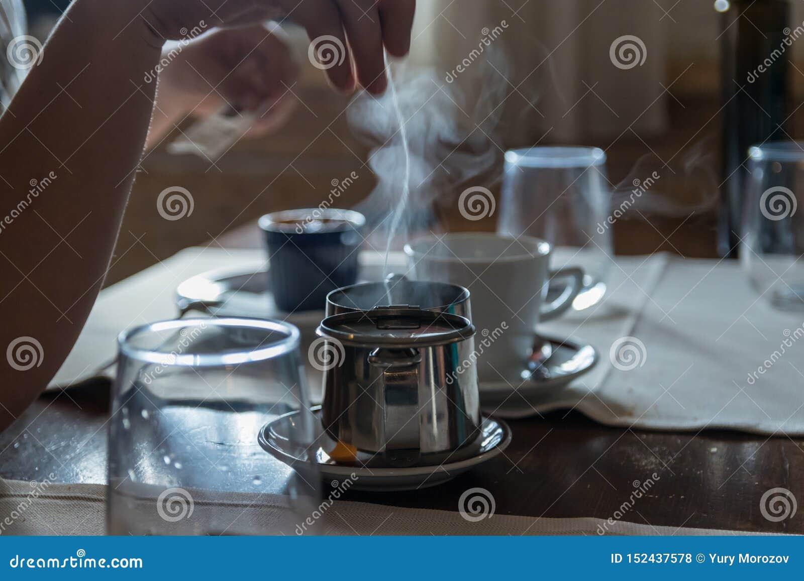 Небольшой чайник с пакетиком чая, некоторые стекла металла на таблице ресторана Белый пар поднимает над горячей водой r