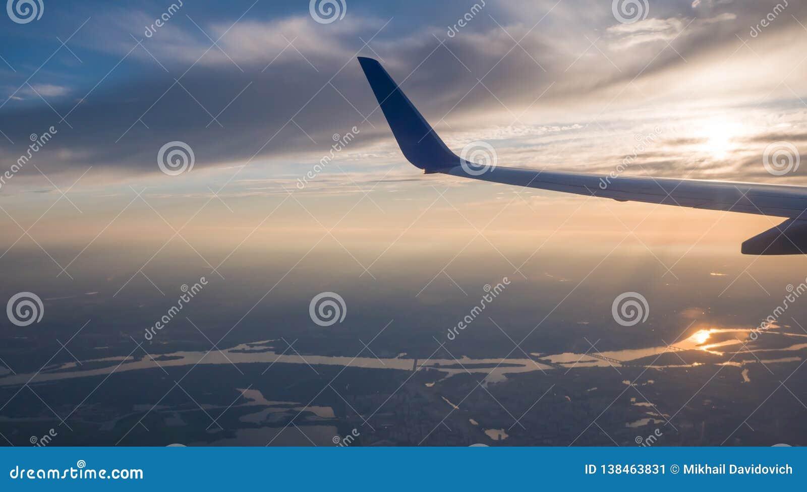 Небо захода солнца на самолете, плоском окне, над Киевом Украина